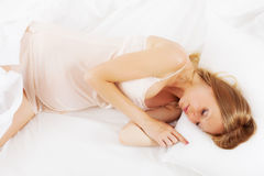 Long-haired pregnant woman sleeping on white pillow Royalty Free Stock Images