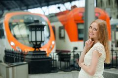 Long-haired pregnant woman waiting train Stock Image