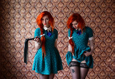 Long-haired red-haired girl in a blue dress, long-haired red-haired girl with a whip in stockings Stock Photos