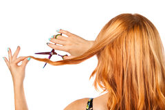 Long-haired red-haired girl with scissors cuts the hair Royalty Free Stock Photos