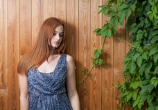 Long haired redhead women leaning against plank background with green leaves of ivy or grape over Royalty Free Stock Images