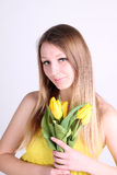 Long-haired romantic girl with yellow tulips Royalty Free Stock Photography