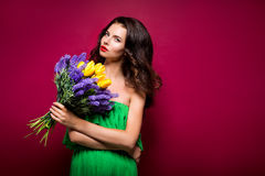 Long-haired seductive brunette with bouquet of flowers. Vinous b. Ackground. Isolated Royalty Free Stock Image