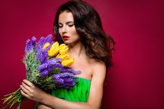 Long-haired seductive brunette with bouquet of flowers. Vinous b. Ackground. Isolated Stock Photography