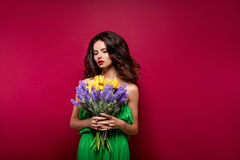 Long-haired seductive brunette with bouquet of flowers. Vinous b. Ackground. Isolated Royalty Free Stock Photography