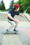 Long-haired skater-teenager in a T-shirt and a sneaker hat jumps an alley against a stormy sky. Long-haired skater-teenager in a T-shirt and sneakers cap jumps Royalty Free Stock Images