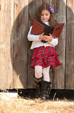 Long-haired smiling girl with book Stock Images