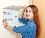 Long-haired smiling woman turning off the light-switch at power. Long-haired woman turning off the light-switch at power control panel in home stock images