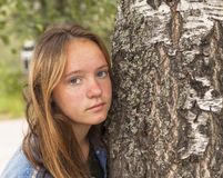 Long haired teen girl in the Park closeup portrait near a tree. Nature. Stock Photos
