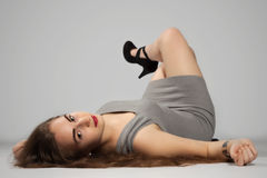 Long-haired teenager girl in gray minis and black high heels Stock Images