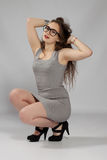 Long-haired teenager girl in gray minis in cool glasses Stock Photos