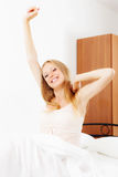 Long-haired woman awaking at home. Long-haired woman awaking on white sheet in bed at home stock image