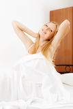 Long-haired woman awaking up in bed. Long-haired woman awaking up on white sheet in bed at home stock photography