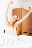 Long-haired woman awaking on white sheet Stock Photography