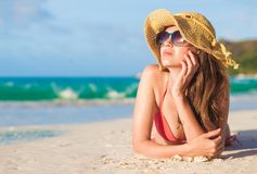 Long haired woman in bikini and straw hat lying on tropical beach royalty free stock image
