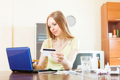 Long-haired woman buying drugs online with laptop. And card at home Royalty Free Stock Photography