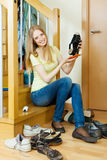 Long-haired  woman cleaning footwear Royalty Free Stock Image