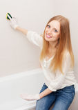 Long-haired woman cleaning tile  in bathroom Stock Image