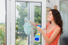Long-haired woman cleaning windows with spray Royalty Free Stock Photos
