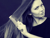 Long haired woman combing her hair. Royalty Free Stock Photos