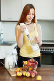 Long-haired woman cooking beverages from peaches Royalty Free Stock Photography