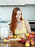 Long-haired woman cooking beverages with peaches Royalty Free Stock Photos