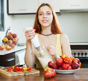 Long-haired woman cooking dairy beverages with nectarines Royalty Free Stock Photos