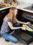 Long-haired woman cooking raw fish in oven. At home kitchen Royalty Free Stock Images