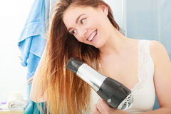 Long haired woman drying hair in bathroom. Haircare. Beautiful long haired woman drying hair in bathroom Stock Images