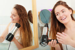 Long haired woman drying hair in bathroom. Haircare. Beautiful long haired woman drying hair in bathroom Royalty Free Stock Image