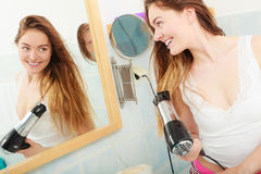 Long haired woman drying hair in bathroom. Haircare. Beautiful long haired woman drying hair in bathroom Stock Photos