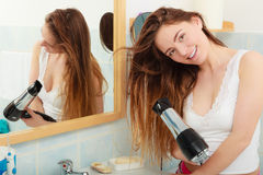 Long haired woman drying hair in bathroom. Haircare. Beautiful long haired woman drying hair in bathroom Stock Image