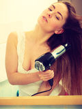 Long haired woman drying hair in bathroom. Haircare. Haircare. Beautiful long haired woman drying hair in bathroom Royalty Free Stock Photo
