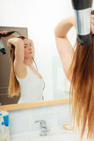 Long haired woman drying hair in bathroom. Haircare. Beautiful long haired woman drying hair in bathroom Royalty Free Stock Images