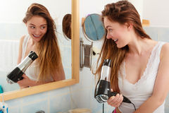 Long haired woman drying hair in bathroom. Haircare. Beautiful long haired woman drying hair in bathroom Stock Photo