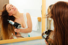 Long haired woman drying hair in bathroom. Haircare. Haircare. Beautiful long haired woman drying hair in bathroom Stock Photos
