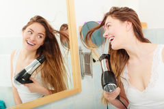 Long haired woman drying hair in bathroom. Haircare. Beautiful long haired woman drying hair in bathroom Royalty Free Stock Photography