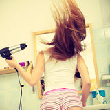 Long haired woman drying hair in bathroom. Haircare. Haircare. Beautiful long haired woman drying hair in bathroom back view Royalty Free Stock Photo