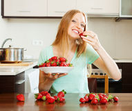 Long-haired woman eating strawberries Royalty Free Stock Images