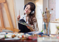 Long-haired woman in headphones  paints on canvas Stock Photography