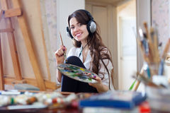 Long-haired woman in headphones  paints with oil colors Royalty Free Stock Photo
