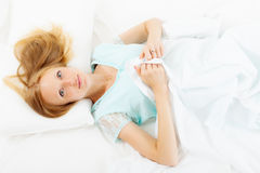 Long-haired woman lying on white sheet Royalty Free Stock Images
