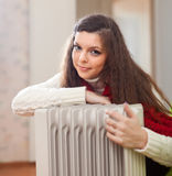 Long-haired woman near oil heater Royalty Free Stock Photos