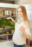 Long-haired woman near opened refrigerator Stock Photos