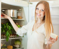 Long-haired woman near refrigerator  at home Stock Images
