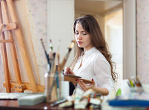 Long-haired woman   paints on canvas Stock Photography