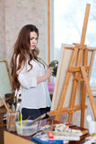 Long-haired woman paints with oil colors Stock Photos