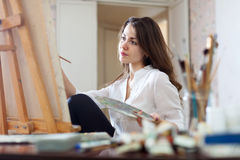 Long-haired woman paints picture on canvas Royalty Free Stock Images
