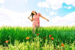Long-haired woman in a pink dress on a field of green wheat and wild poppies. stock images