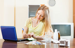 Long-haired woman reading about medications  in internet. Long-haired woman reading about medications on laptop in internet at home Stock Images